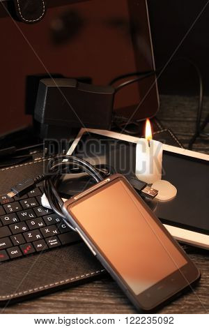Blackout concept. Lighting candle on set of modern electronic gadgets