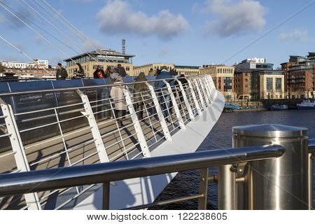 NEWCASTLE ENGLAND - DECEMBER 7 2014: Pedestrians crossing the millennium bridge with the Quayside in the background in Newcastle.