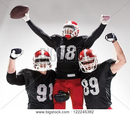 The three caucasian fitness men as american football players posing  as winners on white background and rejoicing ** Note: Visible grain at 100%, best at smaller sizes