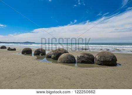 Many moeraki boulders in a line on the beach in New Zealand on sand