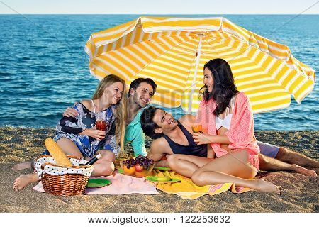 Four friends share food and drinks on the beach. Smiling attractive friends share grapes apples and oranges seated next to wicker basket with bread and wine on the beach.