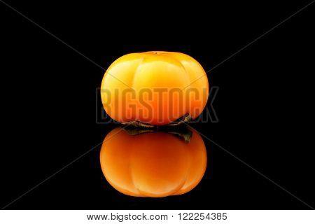 a kaki fruit on a black background