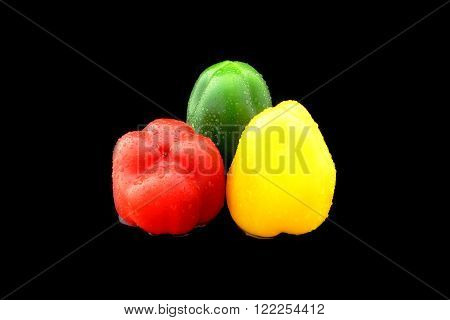 three peppers with different colors on black