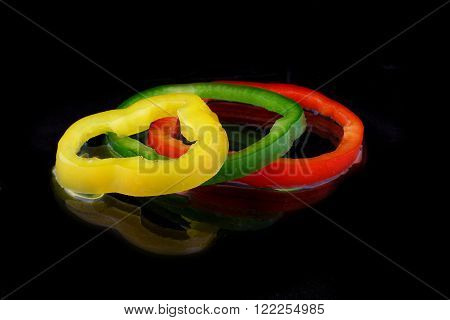 three rings paprika on black background with water