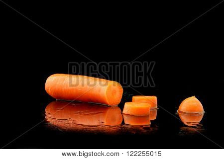 a sliced carrot on black background with water