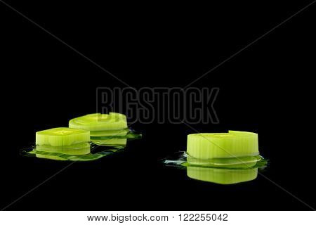three leek pieces with water on black background