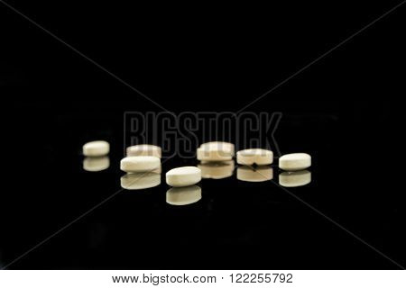 A pile of yellow tablets on black background