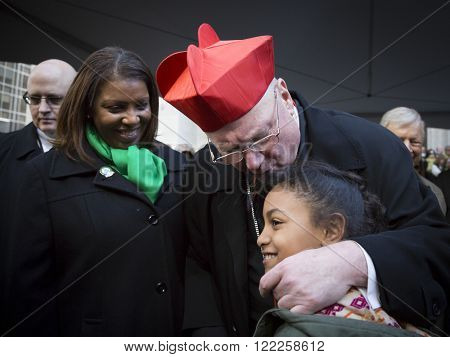 NEW YORK - MARCH 17, 2016: Letitia James, NYC Public Advocate, Timothy Cardinal Dolan Archbishop of New York, and a young parade goer by St Patricks Cathedral on Saint Patricks Day on March 17, 2016.