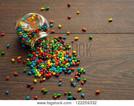 Candy scattered on the floor of the glass jar. Sweet Candy - sunflower seeds in a bright glaze. The floor is wooden, brown board