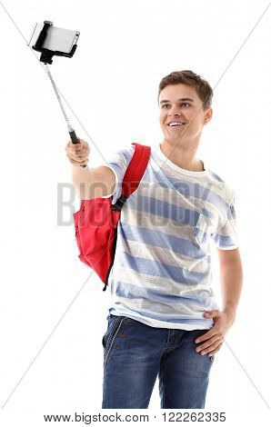 Young handsome boy with backpack using stick for photo by his self, isolated on white