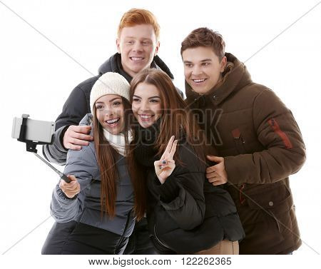 Teenager friends in winter clothing making photo by their self with mobile phone, isolated on white