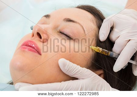 Subcutaneous injection into the girl's face. Doctor cosmetologist doing pull-injection in the face model. Syringe, face, needle, lift - the concept of rejuvenation. Tightening of the skin of the face.
