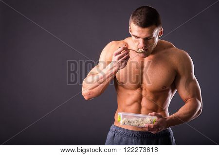 Strong athletic man standing on a black background, a person eats food sport.