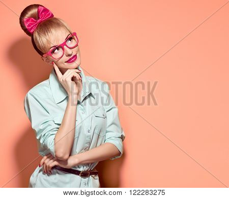 Beauty fashion woman in stylish glasses thinking, idea. Attractive happy blonde hipster girl smiling, emotional. Confidence, success, Pinup hairstyle. Unusual playful, expression nerd.Vintage on pink