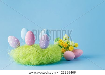 easter decoration with colored egg on blue background