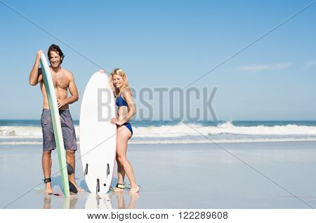 Smiling surfers couple standing with surfboards on the sandy beach. Beautiful surf couple on seaside looking at camera. Surfers ready to surf the ocean in swimwear with copyspace.