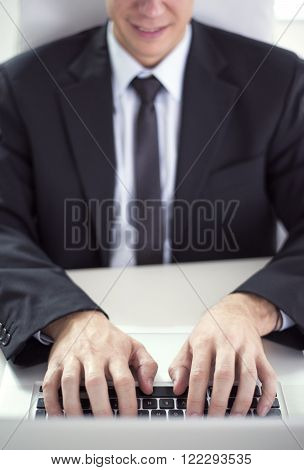 Male hands typing on a laptopsearching for ideas on a computer. His face is not visible.He is wearing a black suit and a black tie.Selective focus on his hand.