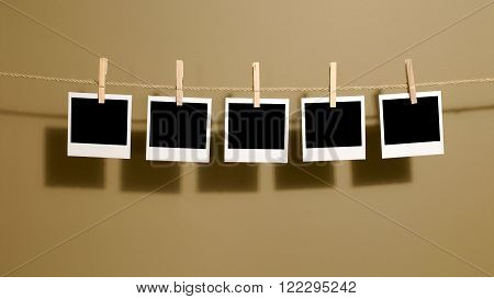 Instant photo print frames hanging on a rope or washing line with darkroom wall background