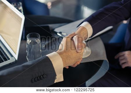 Close up of arms of businessmen shaking hands. They have a meeting