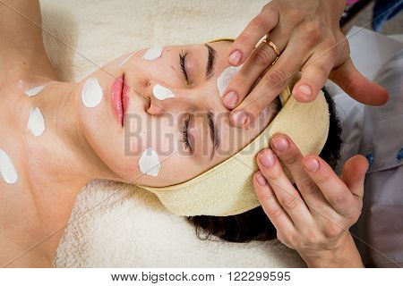 Application of rejuvenating mask on the face of the girl. Cosmetic procedures for the face. Hands beautician applied mask on face of the girl. Facial treatment in a beauty salon.