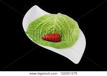 a red pepper with plate on black background