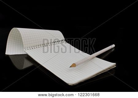 a notepad with a white pencil on black