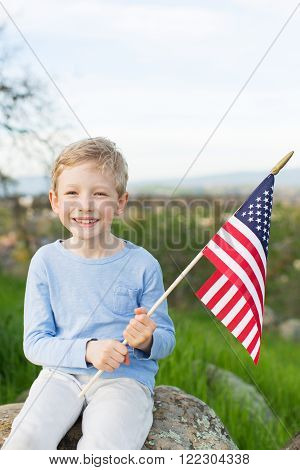 smiling boy holding American flag and celebrating 4th of july