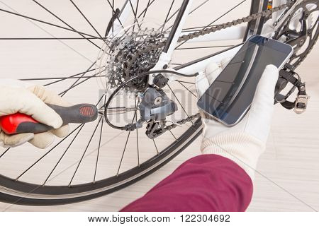 Hand with screwdriver adjusting bicycle's rear derailleur and checking on-line manual on the smart phone poster