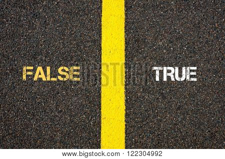 Antonym concept of FALSE versus TRUE written over tarmac, road marking yellow paint separating line between words