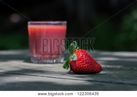 One strawberry on wooden table with vitamin drink