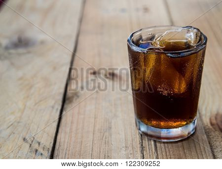 Coca Cola with ice Horizontal shot on the wooden floor Focus on glass.