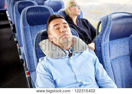 transport, tourism, rest , comfort and people concept -  man sleeping in travel bus with cervical neck inflatable pillow