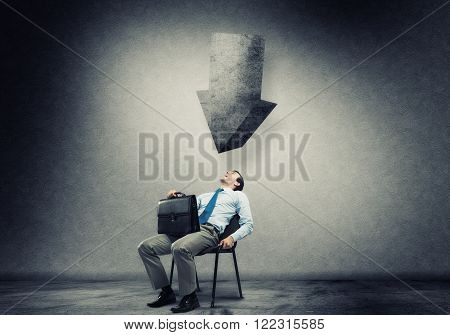 Businessman with suitcase sitting in chair under big arrow