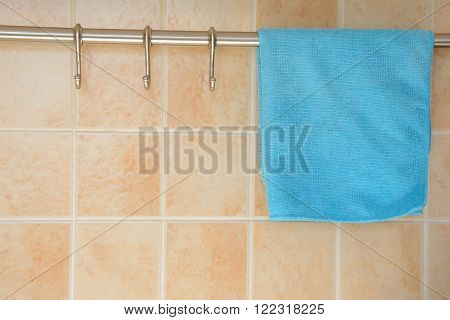 Blue dishcloth hanging on hanger at kitchen wall covered with tiles