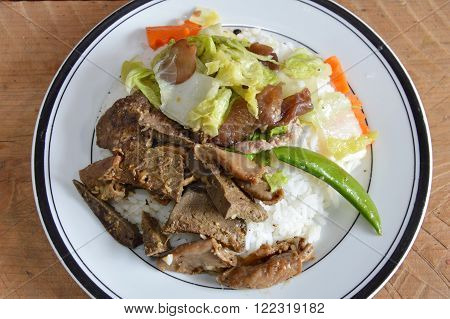 fried pork entrails with garlic and stir-fried mixed vegetable on rice