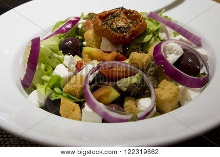 Greek salad served in the white plate