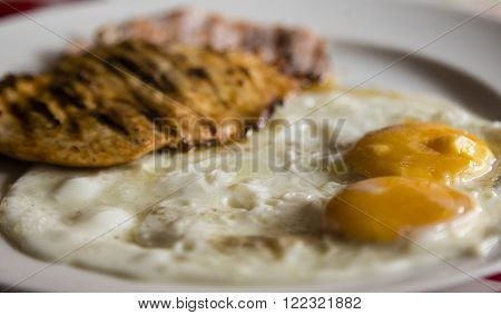 Fried eggs with grilled chicken breast for breakfast