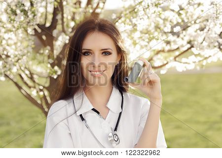 Spring Woman Doctor Smiling and Holding Inhaler - Portrait of female medical professional with an asthma remedy in springtime décor