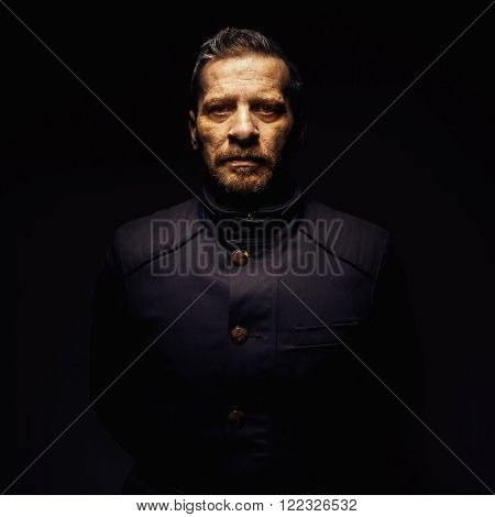Portrait of a middle age man, wearing a jacket something like police or military design.