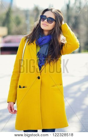 young brunette woman in a yellow coat and sunglas corrects hair Spring City