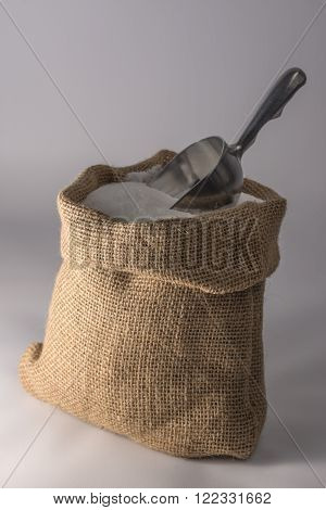 Small open sack of sugar with a metal scoop