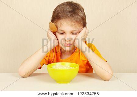 Little boy does not want to eat a porridge