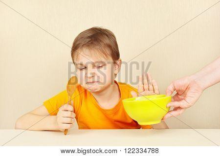 Little cute boy refuses to eat a porridge