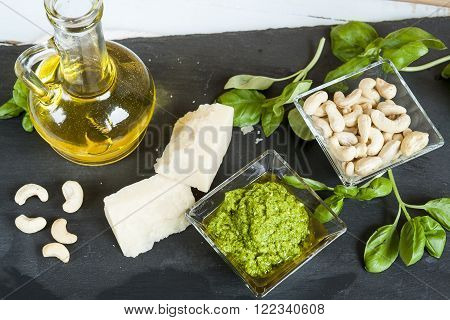 Basil pesto fresh basil leaves parmigiano cheese olive oil and cashew seeds on black stone background. Mediterranean food on black  background.