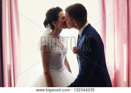 Handsome Groom And Beautiful Bride Kissing & Holding Hands Near Window