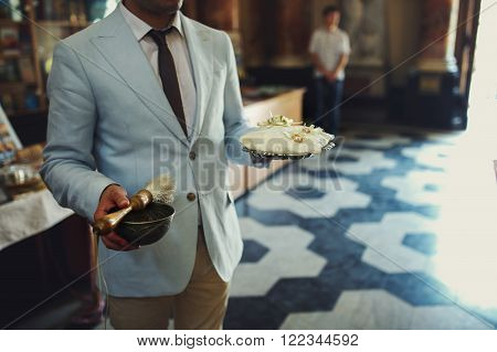 Stylish Bestman Holding Cushion With Two Golden Wedding Rings