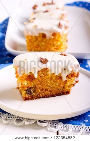 Carrott cake slice with cream topping on plate