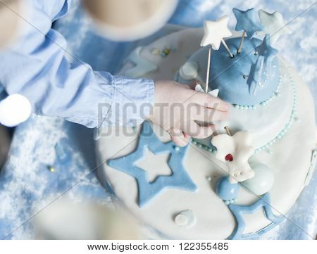 children's hands in birthday cake in the background with a blue tablecloth