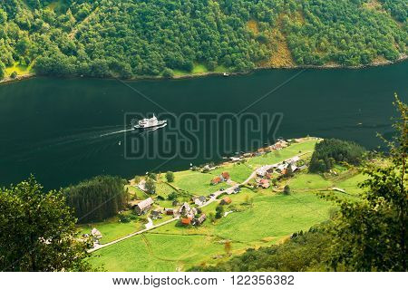 Ship sailing between fjords. Picturesque village near Sognefjord fjord in Norway. Amazing nature of the Norwegian mountains. Beautiful landscape. Travel concept. Scenic view from mountain top.