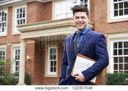 Portrait Of Male Realtor Standing Outside Residential Property